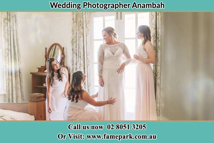 Photo of the Bride assisting by her bridesmaids to fit her wedding gown Anambah NSW 2320