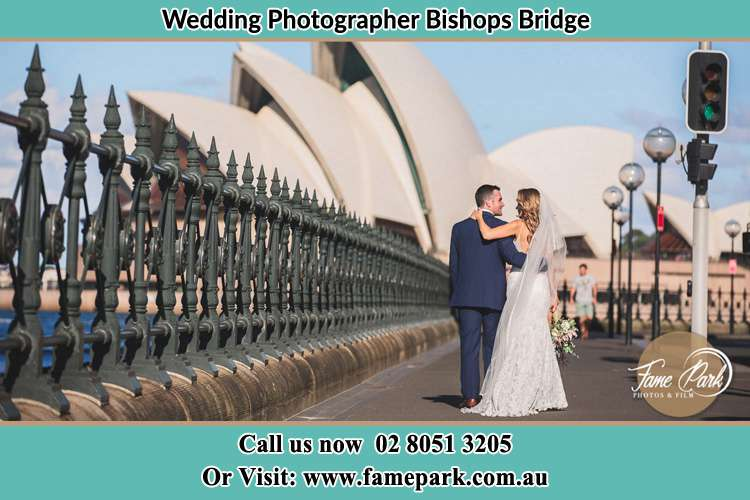 Sweet photo of the Groom and the Bride walking on the street Bishops Bridge NSW 2326