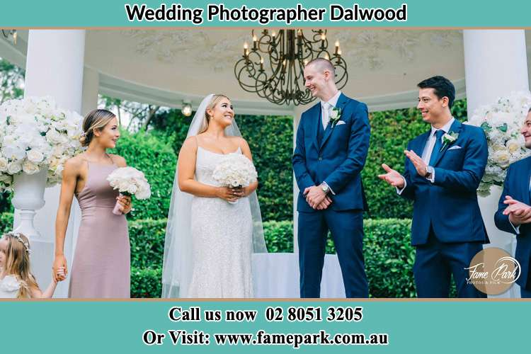 Photo of the Bride and the Groom looking each other cheering up by the groom men and bridesmaids Dalwood NSW 2335