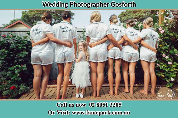 Behind photo of the Bride and the bridesmaids with the flower girl looking back the camera Gosforth NSW 2320