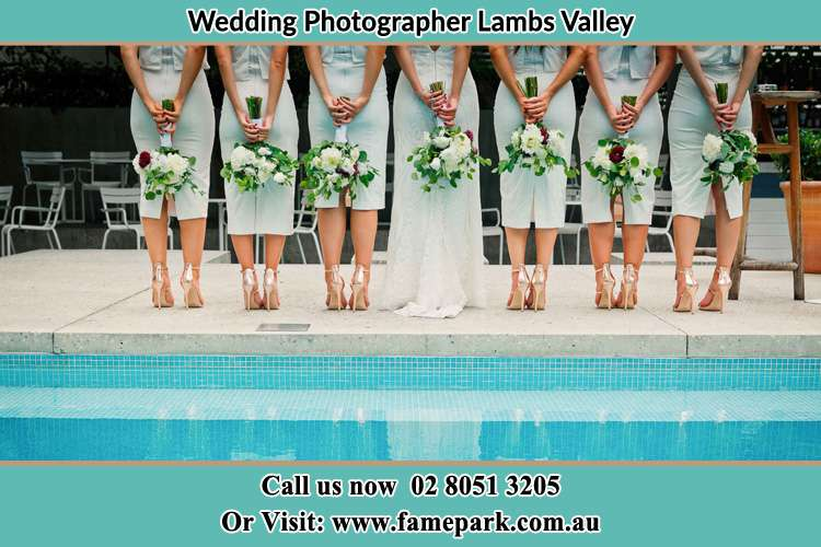 Photo of the Bride and her bridesmaids striking a pose of their behind holding a flower near the swimming pool Lambs Valley NSW 2335
