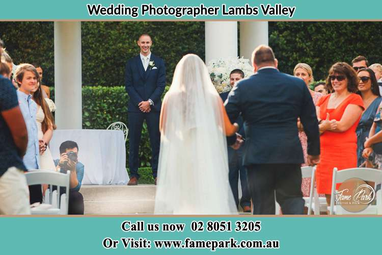 Behind photo of the Bride accompany by her father walking the aisle going to the waiting Groom Lambs Valley NSW 2335