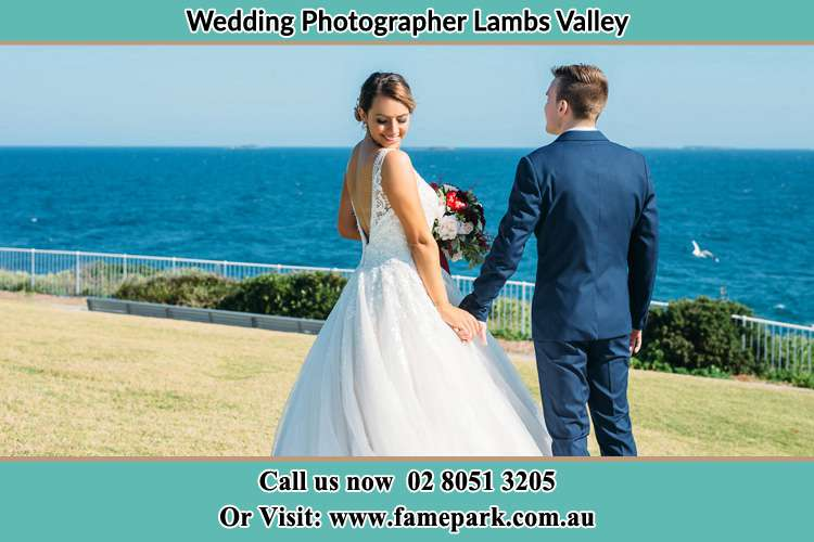 Photo of the Bride looking at her back as the Groom hold her hands Lambs Valley