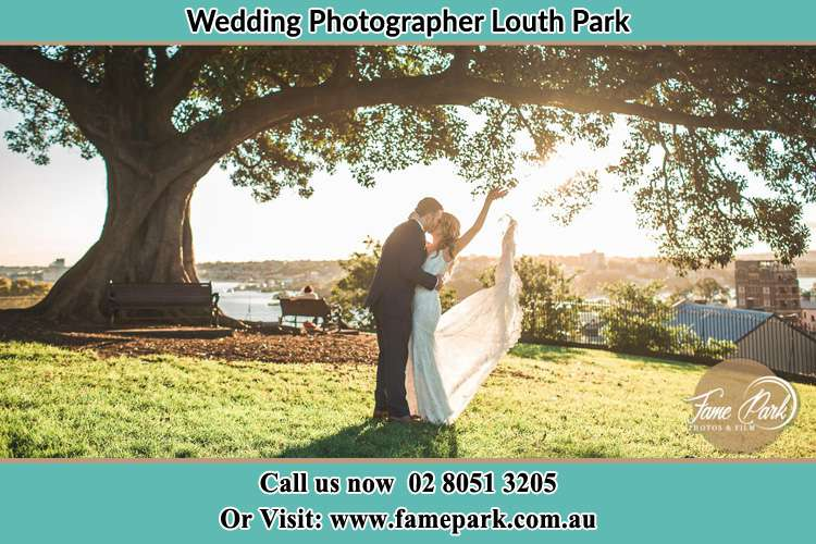 Photo of the new couple kissing under a big tree Louth Park