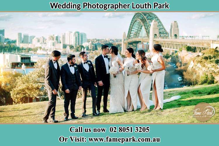 Photo of the Groom and the Bride kissing while teasing by their groom men and bridesmaids Louth Park NSW 2320