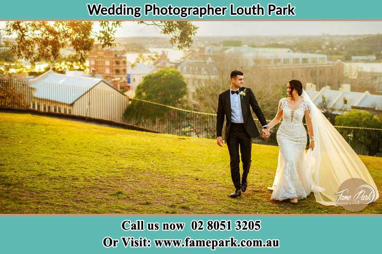 Photo of the Groom and the Bride looking each other and holding hands while walking Louth Park NSW 2320