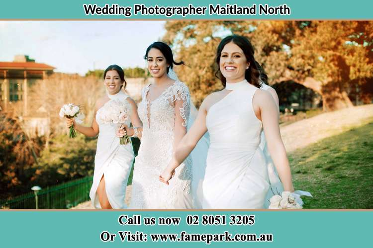 The Bride and her bridesmaids smiles as they walk Maitland North