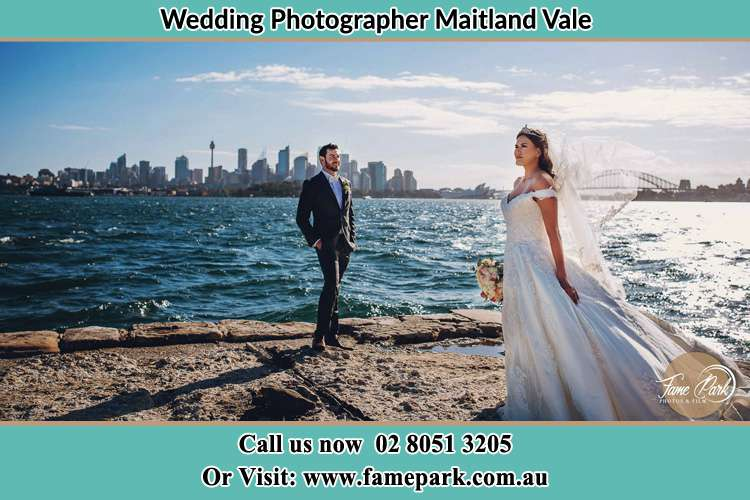 The Groom and the Bride poses for the camera near the shore Maitland Vale