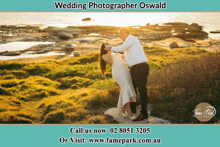 Photo of the Bride and the Groom dancing with a romantic lake background Oswald NSW 2321