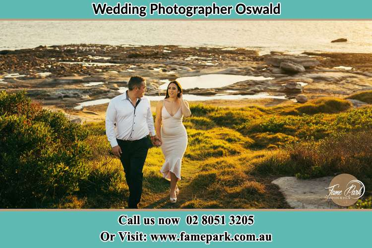 Photo of the Groom and the Bride holding hands while waking Oswald NSW 2321
