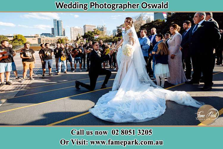Photo of the Groom on his knee taking the hand of his Bride witnessing by the crowd on the street Oswald NSW 2321