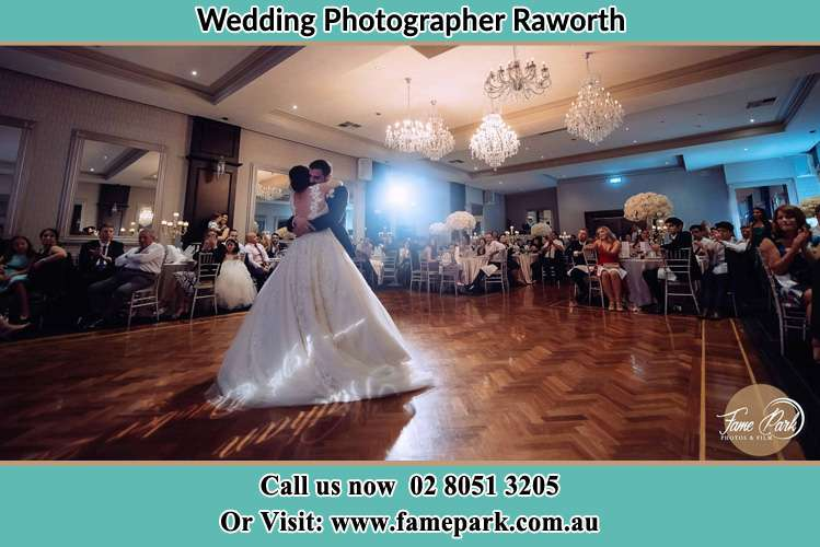 Photo of the Bride and the Groom embrace each other on the dance floor Raworth NSW 2321
