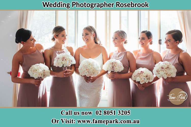 Photo of the Bride and her bridesmaids each holding a bouquet of flowers Rosebrook