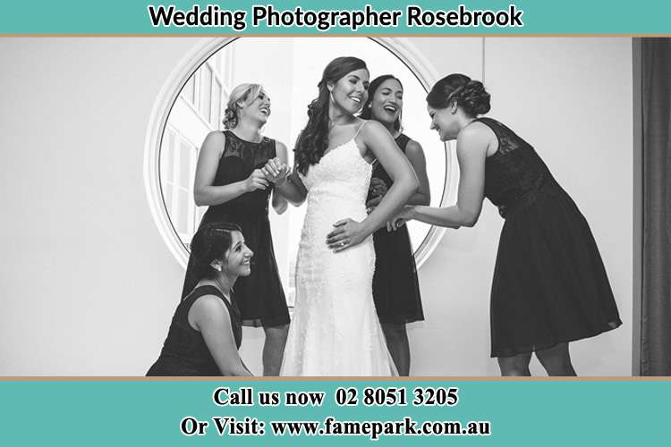 Photo of the Bride together with her bridesmaids checking her wedding gown Rosebrook NSW 2320