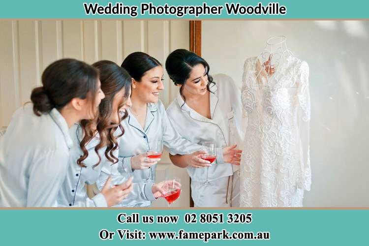 Photo of the Bride with the bridesmaids looking at her wedding gown Woodville NSW 2321